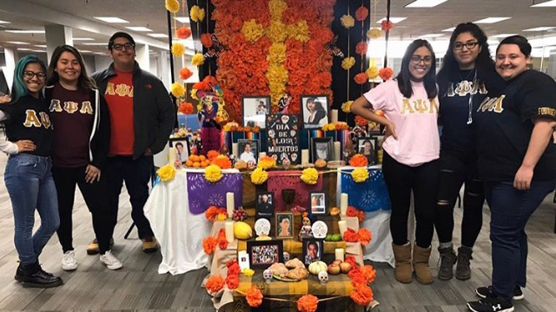 Dia de los muertos display with members from Alpha Psi Lambda.